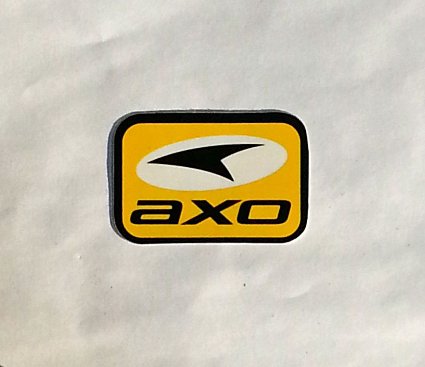 "AXO sticker(small) Yellow/Blk - 2 5/8"" x 1 3/4"""