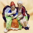"NICE COLONIAL COUPLE SITTING ON BENCH....NICE COLORING....APPROX 5 1/2"" LONG"