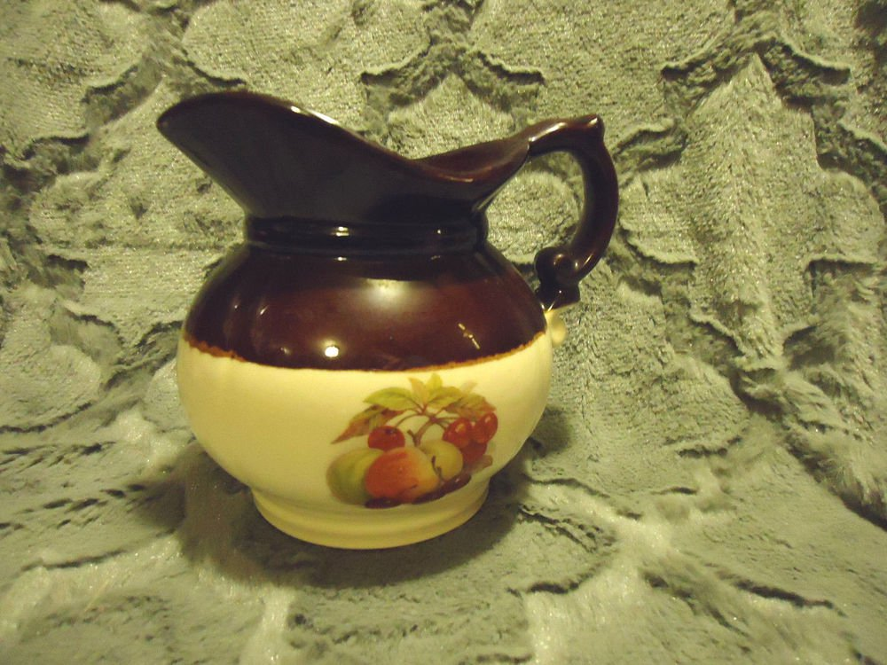 "McCOY SMALL BROWN & BEIGE PITCHER WITH FRUIT DESIGNS....APPROX 6"" TALL"