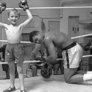"""MUHAMMAD ALI """"GOES DOWN"""" IN RING THANKS TO A KID - 8X10 PUBLICITY PHOTO (ZY-157)"""