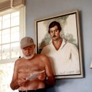 ERNEST HEMINGWAY IN FRONT OF PORTRAIT OF HIMSELF CIRCA 1953 8X10 PHOTO (AA-277)