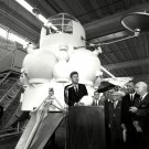 PRESIDENT JOHN F. KENNEDY SPEAKS IN FRONT OF LUNAR LANDER - 8X10 PHOTO (AA-199)