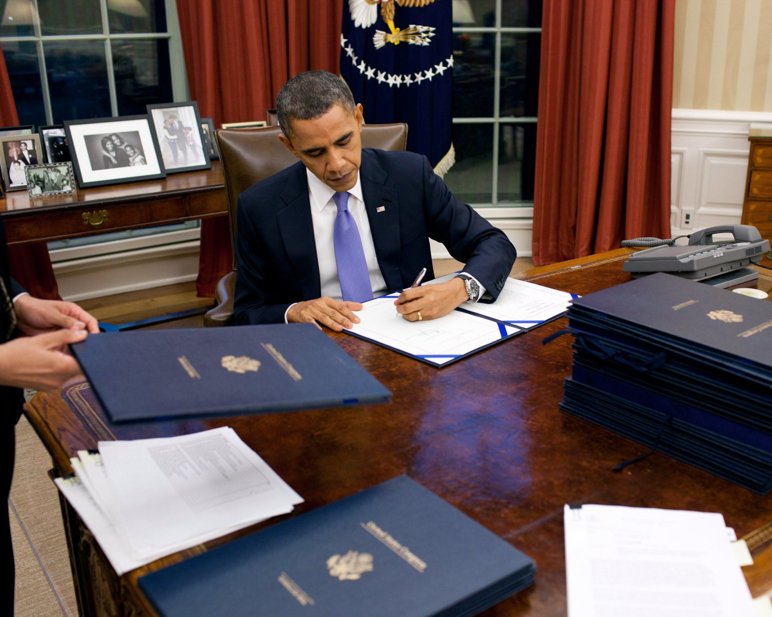 PRESIDENT BARACK OBAMA SIGNS LEGISLATION IN THE OVAL OFFICE 8X10 PHOTO (ZY-376)