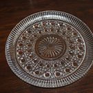 Vintage pressed glass cake plate with raised rim.