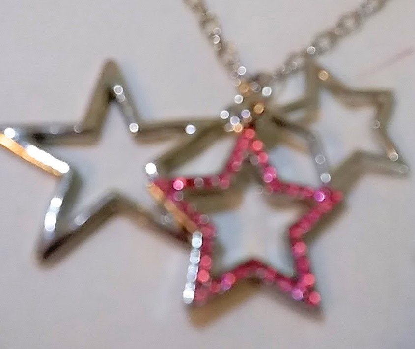 Silver necklace with 3  star shaped silver-tone accents with pink crystals. 18 inch chain