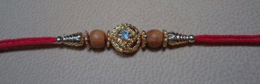 Tulsi/Basil Brown Beads Rakhi in Gold Tone With Clear Crystal By Teknowear