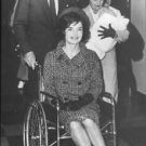 Jacqueline Kennedy sitting on wheelchair and John F. Kennedy pushing the chair.