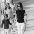 Jacqueline Kennedy Onassis walking with a child.  - 8x10 photo