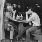 Catherine Deneuve and David Bailey sitting at table. - 8x10 photo