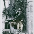An old French soldier salutes beside the German gun. - 8x10 photo
