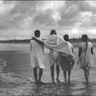 Mahatma Gandhi walking on a beach with some youngsters.  - 8x10 photo
