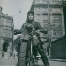 A woman riding a motorcycle in London, 1942. - 8x10 photo