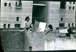 Women on rooftop, holding flag.  - 8x10 photo