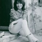 Juliette Greco sitting comfortable and smiling.  - 8x10 photo