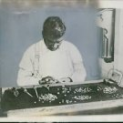 Man working with pearl, holding tools. - 8x10 photo