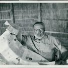 Ernest Hemingway reading newspaper.  - 8x10 photo