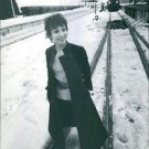 Esther Ofarim standing on the railway, a train can be seen in the background. -
