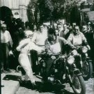 Colette Duval getting on bike while Gil Delamare looking at her, 1959. - 8x10 ph