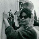 Pascale Petit, in sunglasses, writing autograph. - 8x10 photo
