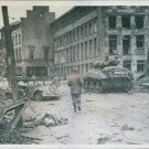 Army troop proceeding through the street of war battered cologne. - 8x10 photo