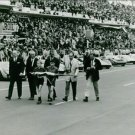 Men and two children walking and holding flags during Le Mans.  - 8x10 photo