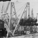 World War II. Engines lifted from a freighter by a giant crane - 8x10 photo