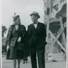 Maurice Chevalier walking with woman. - 8x10 photo