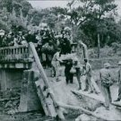 U. S. Marines assist Okinawa civilians across blasted bridge.The Battle of Oki