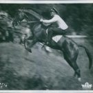 A man riding a horse in a scene from the film Olympia, 1938. - 8x10 photo