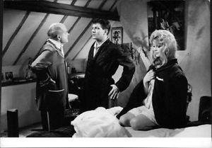 Brigitte Bardot sitting on bed and two men communicating.  - 8x10 photo