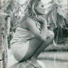 Ursula Andress sitting on stone. - 8x10 photo