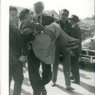Ernest Hemingway carrying a faint woman. - 8x10 photo