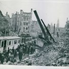 People of Dresden are getting on to trams in the midst of chaotic ruin still lyi