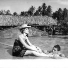 Catherine Deneuve relaxing by pool, with Roger Vadim. - 8x10 photo