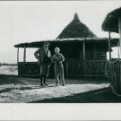 Ernest Hemingway standing on landscape with a woman.    - 8x10 photo