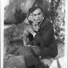Charles Boyer sitting with pet dog.  - 8x10 photo