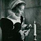 Katharine Hepburn standing near lighten candle.  - 8x10 photo