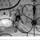 Claudia Cardinale relaxing on bed.  - 8x10 photo