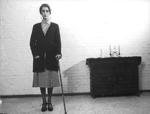 Catherine Deneuve standing with crutch.  - 8x10 photo