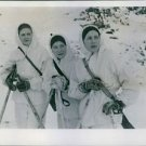 Three of the women volunteers standing together and looking at something. - 8x10