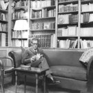 Jacques Monod siiting on sofa reading book. - 8x10 photo