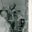 Woman showing book to Ernest Hemingway.   - 8x10 photo