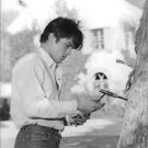 Alain Delon standing by tree, holding knife. - 8x10 photo