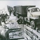 A truck convoy of U.S. lend loase supplies, manned by American, pause on a mount