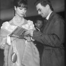 Elsa Martinelli standing with a man looking at magazine. - 8x10 photo