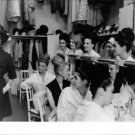 Capucine smiling in hat and coat, with models getting ready.  - 8x10 photo