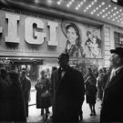 Maurice Auguste Chevalier in front of a movie theatre looking at his film`s post