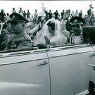 Hussein bin Talal sitting in car with his wife and waving.  - 8x10 photo