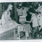 The Royal couple of Thailand kneeling, Her Royal Highness offering a bowl to a n