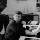 John F. Kennedy holding papers and looking towards man. - 8x10 photo